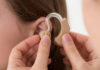 Doctor Inserting Hearing Aid