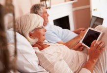 Senior Couple Lying In Bed Using Digital Devices - The Best Tablets for Seniors