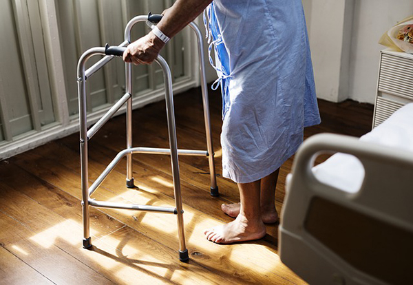 Patient trying to stand up using support walking